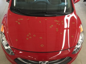 Hail damage on the hood of a red sedan